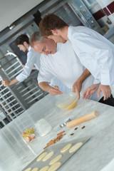 experienced baker teaching male apprentice
