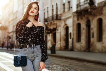 Outdoor portrait of yong beautiful fashionable woman wearing stylish black white polka dot blouse, blue jeans, red earrings, with small quilted bag. Model posing in street of european city. Copy space Wall mural