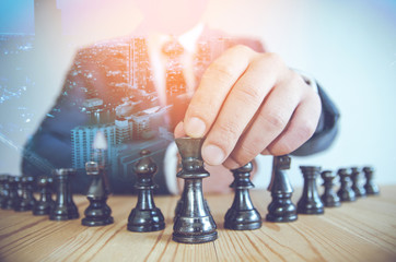 business playing chess board game , business concept plan to success , over city background