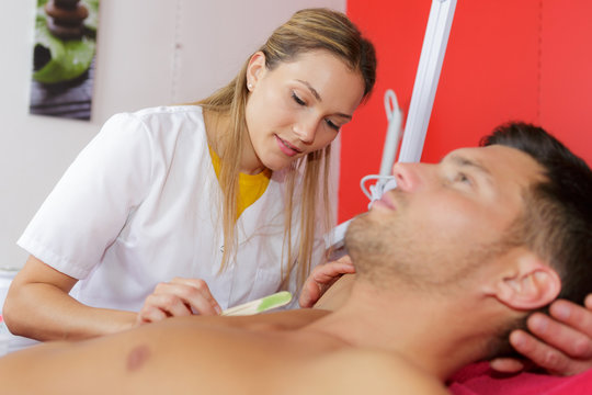 man receiving waxing for hair removal in beauty salon