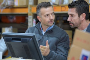 workers using digital devices in warehouse on desk