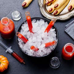 Bloody Mary cocktail in glass tubes with Witch's fingers cookies for Halloween party. Slate background. Top view.