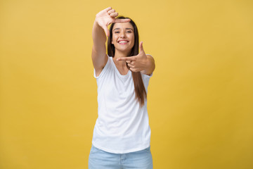 Young beautiful woman over isolated yellow background smiling making frame with hands and fingers with happy face. Creativity and photography concept.