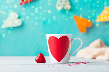 Romantic cup with chocolate heart shaped candy. Blue background with paper hearts garland.
