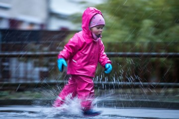 Girl is having fun in water on street in cold autumn day, girls splashing water in rain, happy and cheerful girl enjoying cold weather, kid in pink rain coats and rubber boots, running in rain