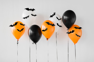 holidays, decoration and party concept - orange, black and white air halloween balloons with black bats on white background