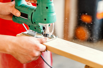 Close-up on worker cutting out a patterned contour on a wooden board using an electric jigsaw with a laser guide