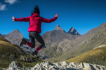 Jeune femme sautant de joie en montagne , alpes , face aux aiguilles d' Arves