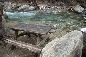 wooden picnic table on the edge of the creek