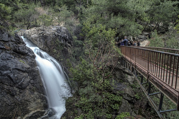 Tourists are taking Sutuven Waterfall's photos from the bridge. On Ida Mountains in Zeytinli