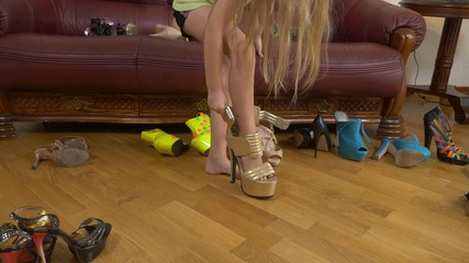 A little girl is playing with high-heeled shoes. The legs of a small child in shoes for adults. girl in high heels.