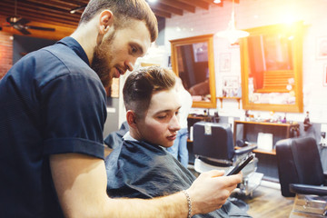 Man at the hairdressing salon. Hairstylist with client choosing a trendy haircut