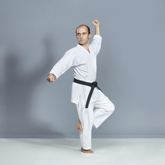 Athlete with a black belt and white karategi performs formal karate exercises