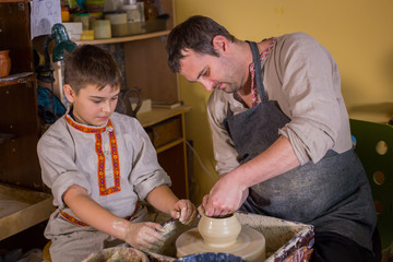Pottery class and workshop: professional male potter working with boy and showing how to make ceramic wares in pottery studio. Handmade, education and study concept