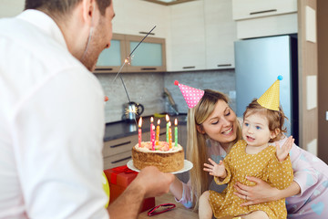 A family with a cake congratulates a happy child on his birthday. Happy parents congratulate their daughter.