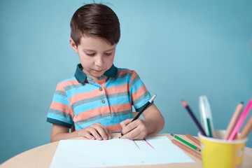 Caucasian boy carefully drawing with colorful pencils at home.