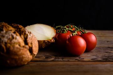 Tomaten,Zwiebel und Brot rustikal auf Holz