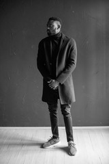 Young black man in coat on dark background. Professional photo studio. Fashion portrait of young man in black shirt in studio . black and white portrait
