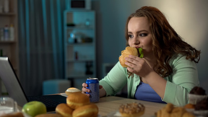 Overweight lady eating unhealthy food, watching show on laptop, sedentary life