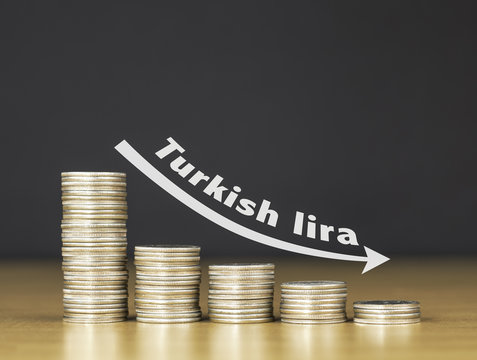 Stacked coins on wooden table with white illustration shows depreciation of Turkish lira / FINANCIAL CONCEPT