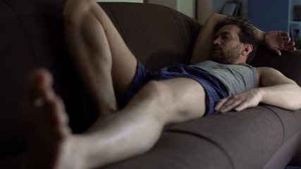 Lazy person in underwear sleeping on couch after hard workday, apathy, problems