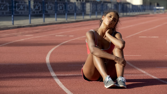 Biracial sportswoman sitting tired after trainings in middle of track, exhausted