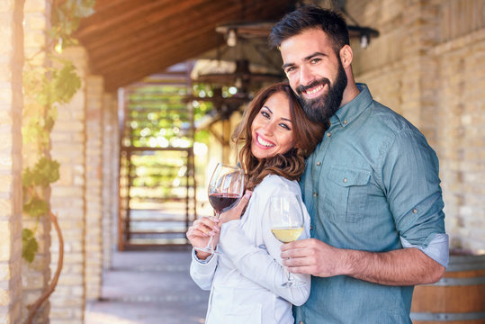Portrait of young smiling man and woman tasting wine at winery vineyard - Young people enjoying harvest time together. Romantic love.