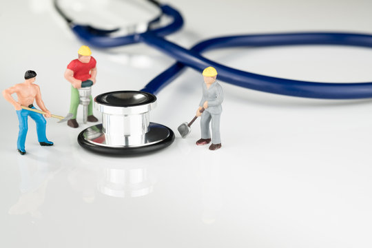 Stethoscope and three blue collar workers / Healthcare & Insurance Concept