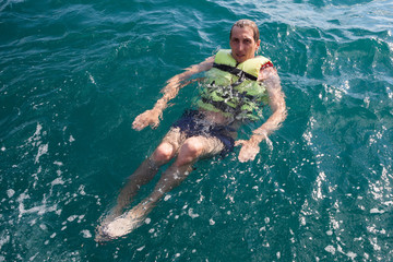 European young man staying afloat with cork lifesaving vest in open ocean