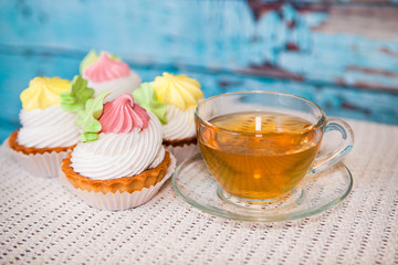 Cupcakes and cup of tea on blue wooden background, sweet food with hot drink