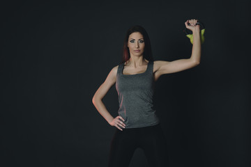 Young female doing swing exercise with a kettle bell. Fitness woman