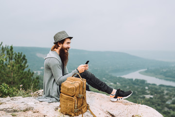 Young tourist sits on a high rock with a phone in his hand.Near the guy is a stylish brown backpack.The young man has a long beard and a white smile.On the background of a guy green summer landscape.