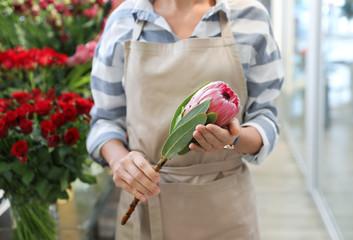 Female florist holding beautiful flower in shop