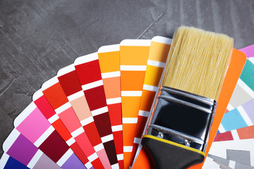 Brush and paint color palette samples on gray background, closeup