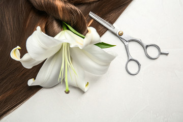Flat lay composition with brown hair, scissors and flower on gray background