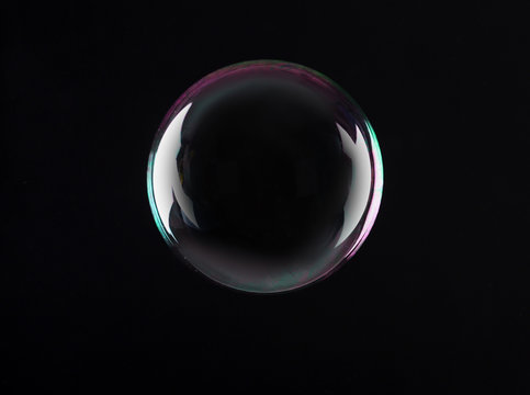 Beautiful translucent soap bubble on dark background. Space for text