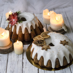 Christmas English fruitcake with candied fruit, dried fruit and nuts, decorated with white icing on a wooden background with fir branches, candles. Festive English cuisine