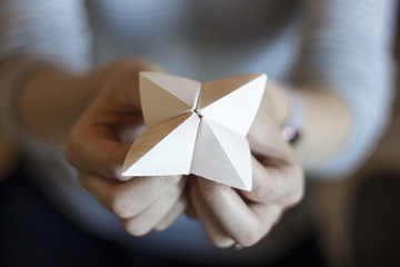 Woman's hands holding a paper fortune teller