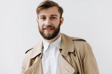 Man portrait. Young blond guy in shirt and coat is looking at camera and smiling, on the white background