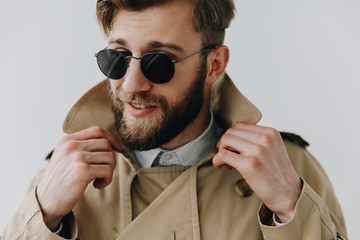 Man portrait. Young blond guy in sun glasses and coat is smiling, on the white background