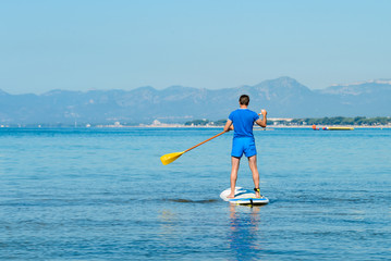 Stand up paddle boarding. Young man floating on SUP board