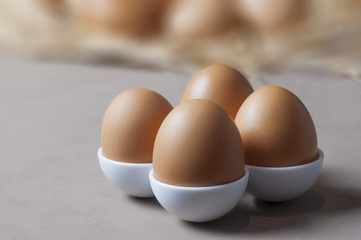 Brown or yellow Fresh farm eggs on quaternary eggcup, eggs background