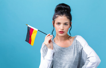 Young woman with a German flag on a blue background