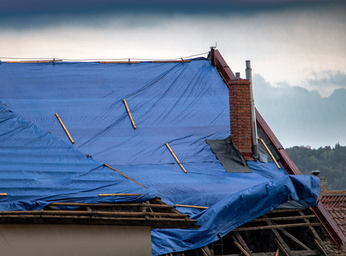 The protective tarpaulin on the roof flutters at the storm with rain. The tarp covers the roof of the old house in the reconstruction.