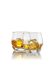 close up view of two glasses with ice and whiskey on white  background