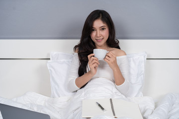 woman drinking a cup of coffee and using laptop computer on bed
