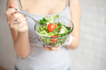 Close-up rear view woman holding bowl of fresh vegetable salad holding fork in hand.