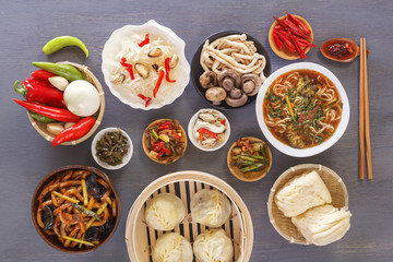 Chinese food on a gray wooden table. Traditional steam dumplings, noodles, vegetables, seafood. Top view.