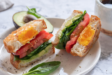 Egg in a hole sandwich with avocado, spinach and tomato