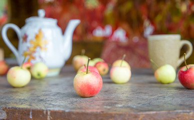 Cup of tea with autumn leaves and apples on wooden table
